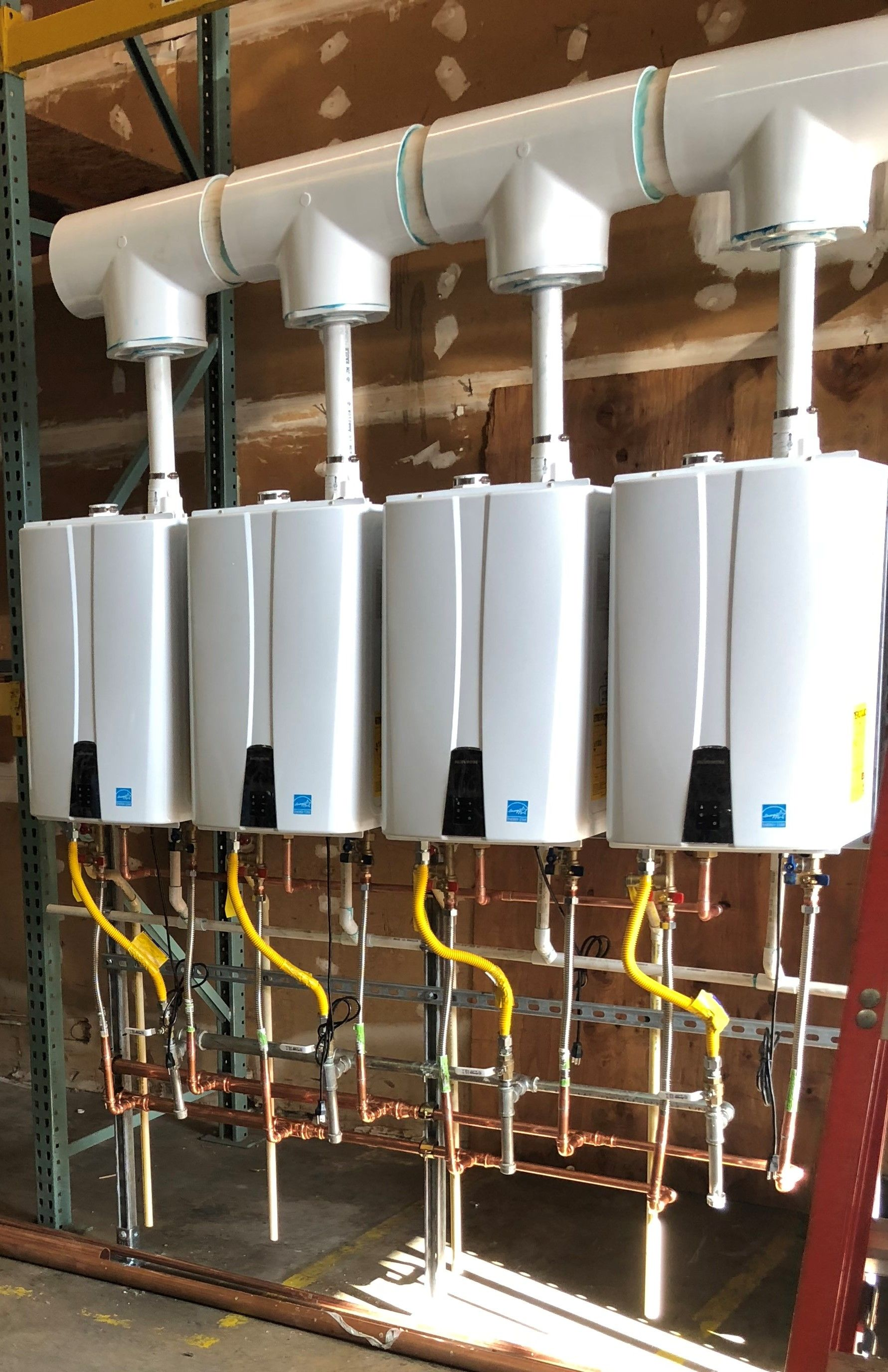 Four tankless water heaters in a row.